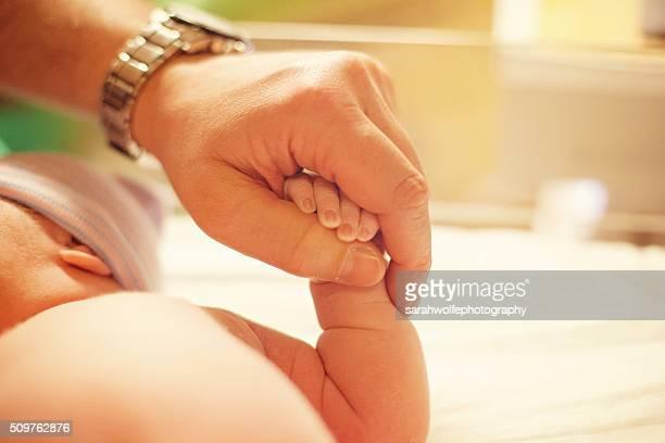 newborn baby holding father's hand
