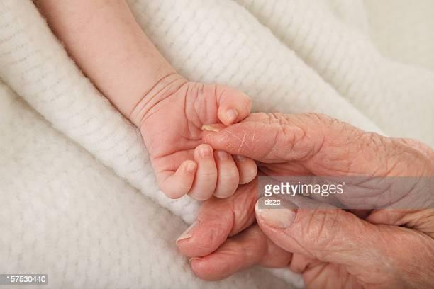 newborn baby holding great grandmother's hand