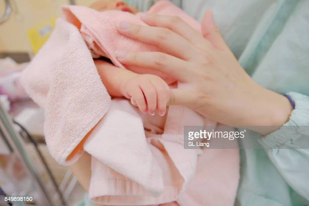 newborn baby holding his mother's hand