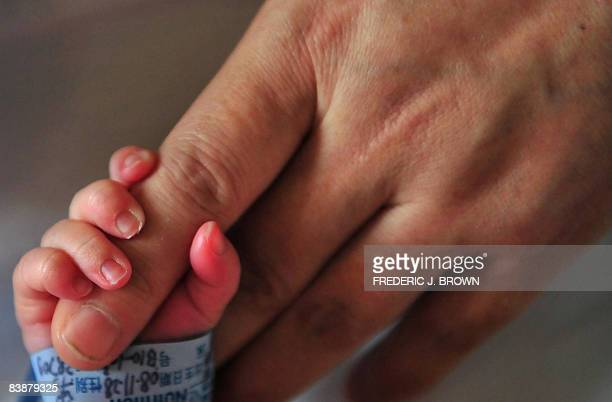 A newborn baby holds onto his mother's finger at a hospital in Beijing on December 1 2008 The Chinese government has insisted extensive measures have...