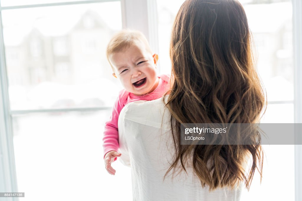 newborn baby in the hand of his mother at the window : Stock Photo
