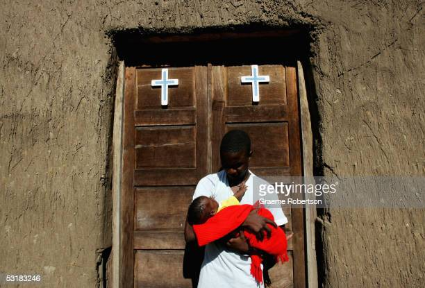 Newborn baby is held by her father outside a church in a small village outside Quelimane, on July 2, 2005 in, Mozambique. Since Mozambique's 15-year...