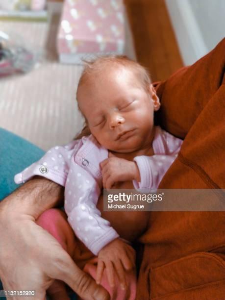 Newborn baby sleeping in parent's arms.