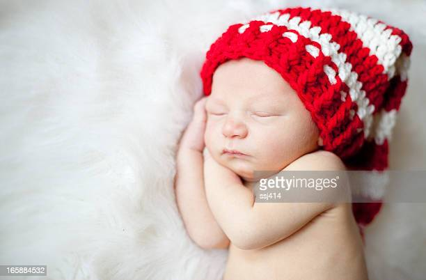 Newborn Baby Sleeping with Red White Striped Hat On.