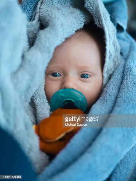 A newborn baby swaddled in a beach towel.