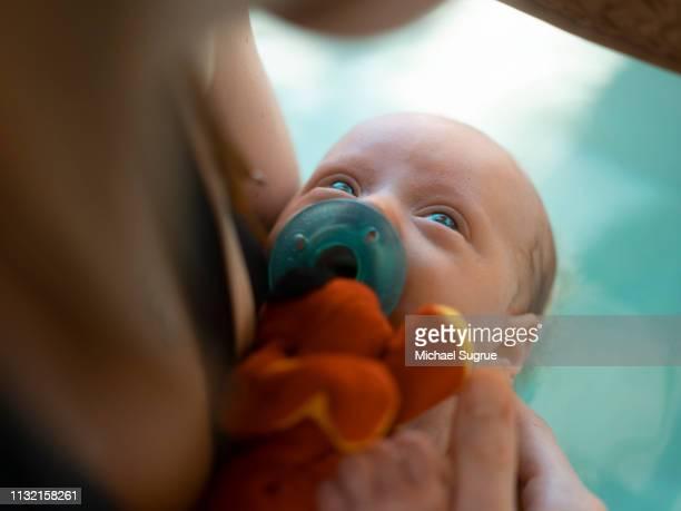 A newborn baby takes a bath.