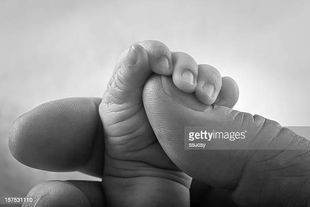 Winzige neugeborene Baby Hand Holding Erwachsenen Finger große Männer