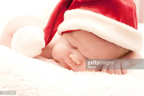 A newborn baby wearing a Santa Claus hat