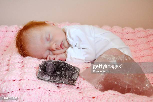 newborn baby with red hair sleeping next to gemstones - rock baby sleep stock pictures, royalty-free photos & images