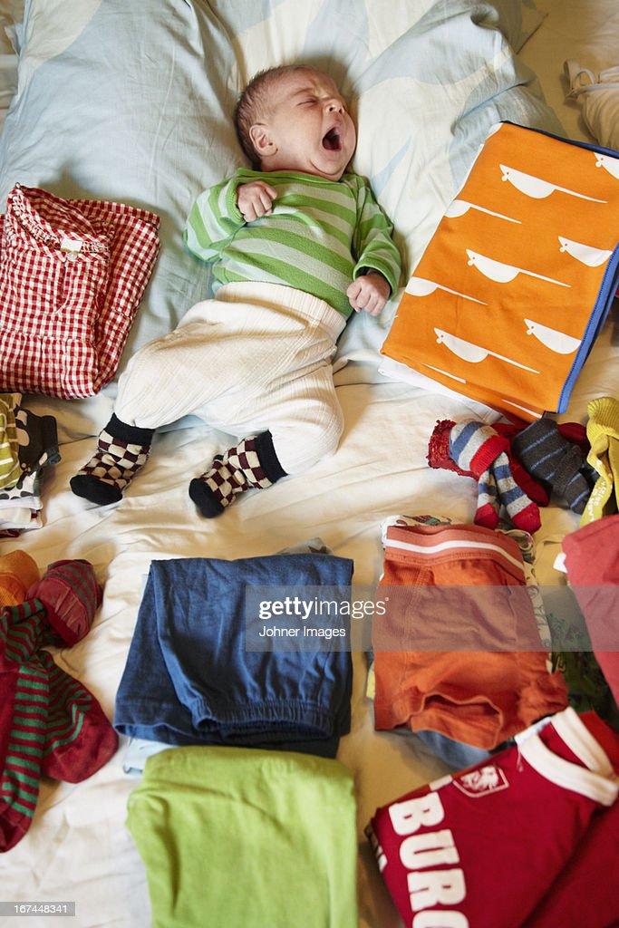 Newborn baby yawning around clear laundry : Stock Photo