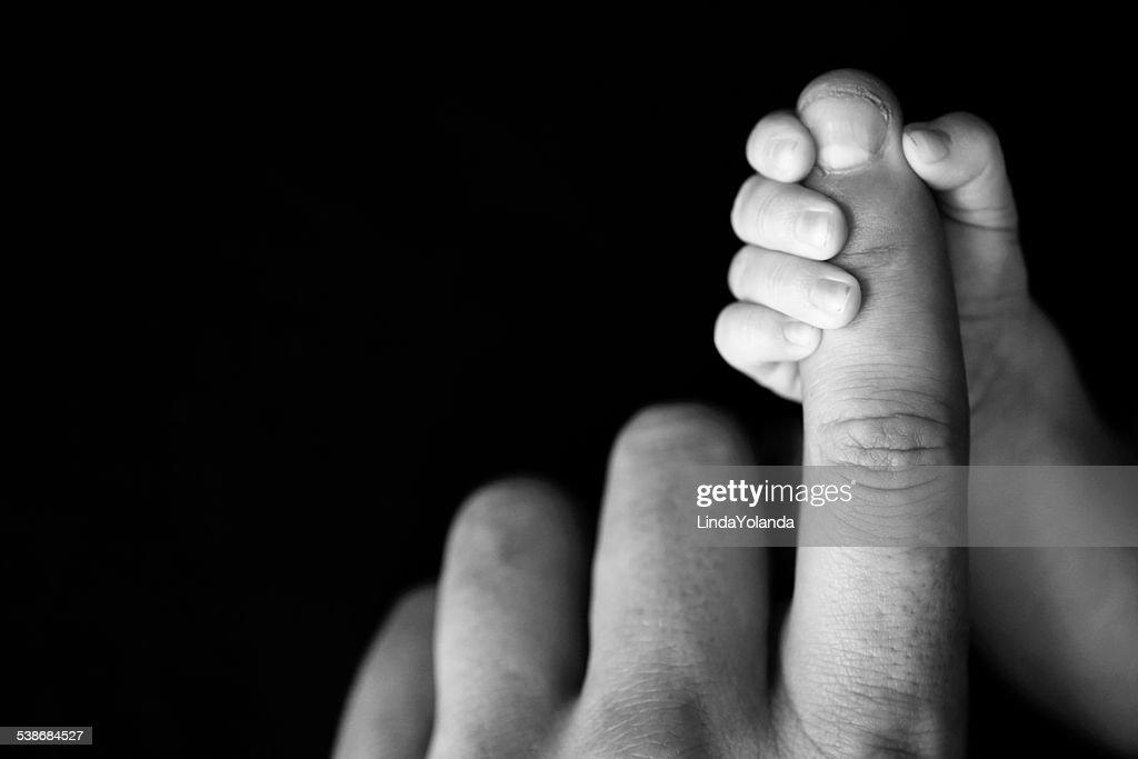 Newborn babys hand gripping dads finger
