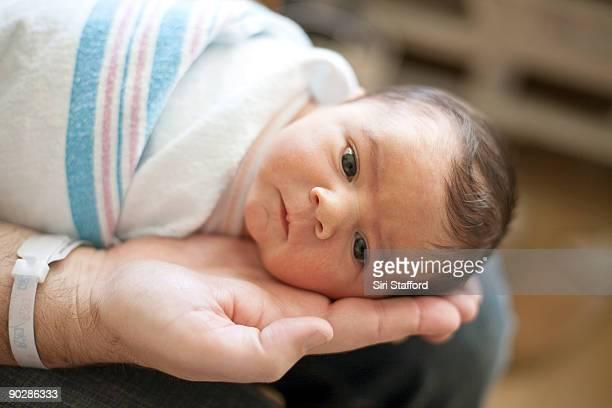 Newborn boy in fathers hand in hospital
