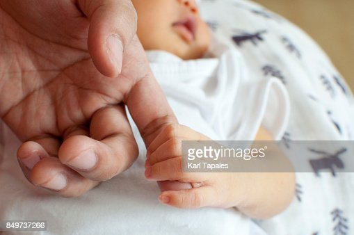 A newborn child holding an adult hand