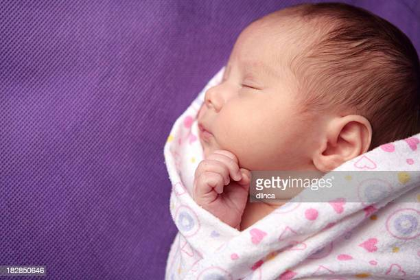 a newborn girl sleeping while being swaddled - purple hat stock pictures, royalty-free photos & images