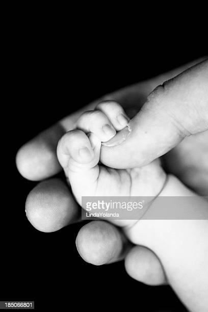 Newborn Gripping Dad's Thumb