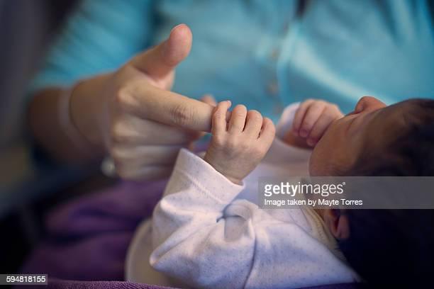 Newborn holding mum's hand at hospital
