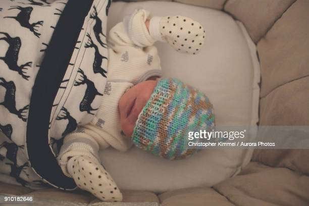 Newborn sleeping in bassinet with knit hat pulled over eyes, Langley, British Columbia, Canada