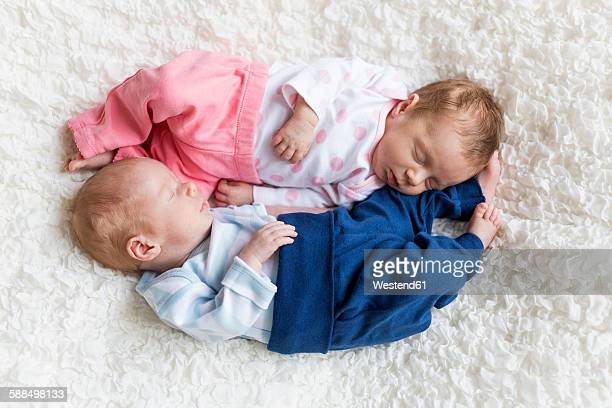 Newborn twins sleeping on white blanket