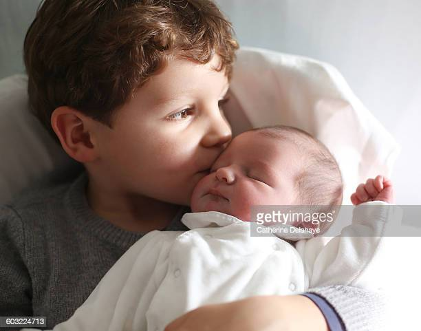A newborn with her brother at the maternity ward