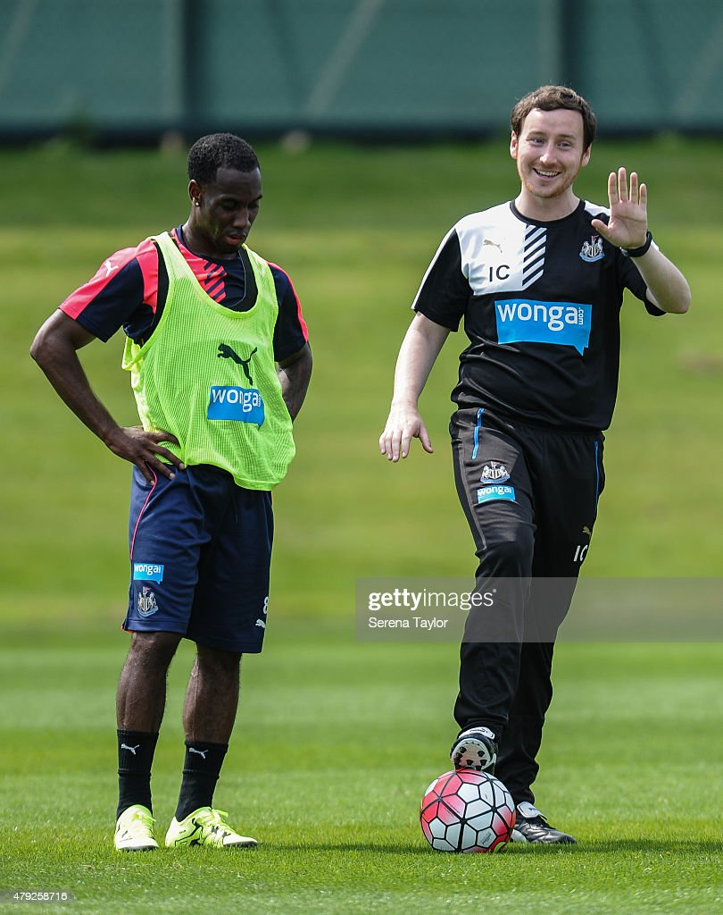 Newcastle Assistant Coach Ian Cathro (R) has one foot on a ball and gestures with his hands and smiles whilst on the training pitch with Vurnon Anita (L) during the Newcastle United Pre-Season Training session at The Newcastle United Training Centre on July 1, 2015, in Newcastle upon Tyne, England.