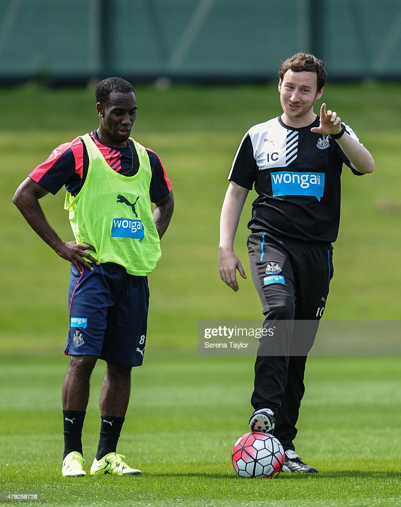 Newcastle Assistant Coach Ian Cathro (R) has one foot on a ball and points with a smile whilst on the training pitch with Vurnon Anita (L) during the Newcastle United Pre-Season Training session at The Newcastle United Training Centre on July 1, 2015, in Newcastle upon Tyne, England.