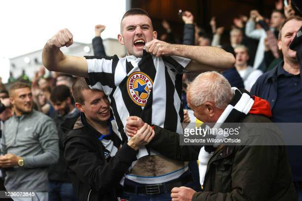 Newcastle fan celebrates their equalising goal by kissing his shirt as two other fans clasp hands around him during the Premier League match between...