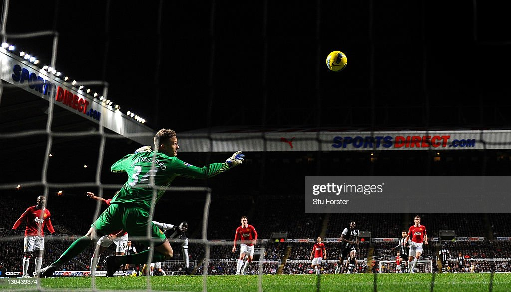 Newcastle forward Demba Ba (l) scores past Man United keeper Anders Lindegaard during the Barclays Premier league game between Newcastle United and Manchester United at St James' Park on January 4, 2012 in Newcastle upon Tyne, England.