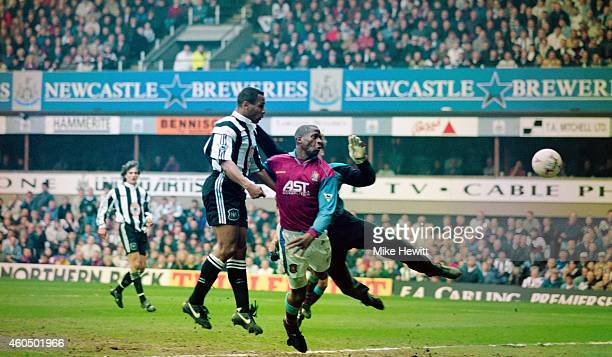 Newcastle forward Les Ferdinand beats Villa defender Ugo Ehigou and goalkeeper Mark Bosnich to head the winning goal during the Premier League game...