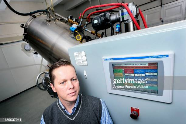 Newcastle Funeral Home owner Trevor Charbonneau stands next to the funeral home's alkaline hydrolysis machine.
