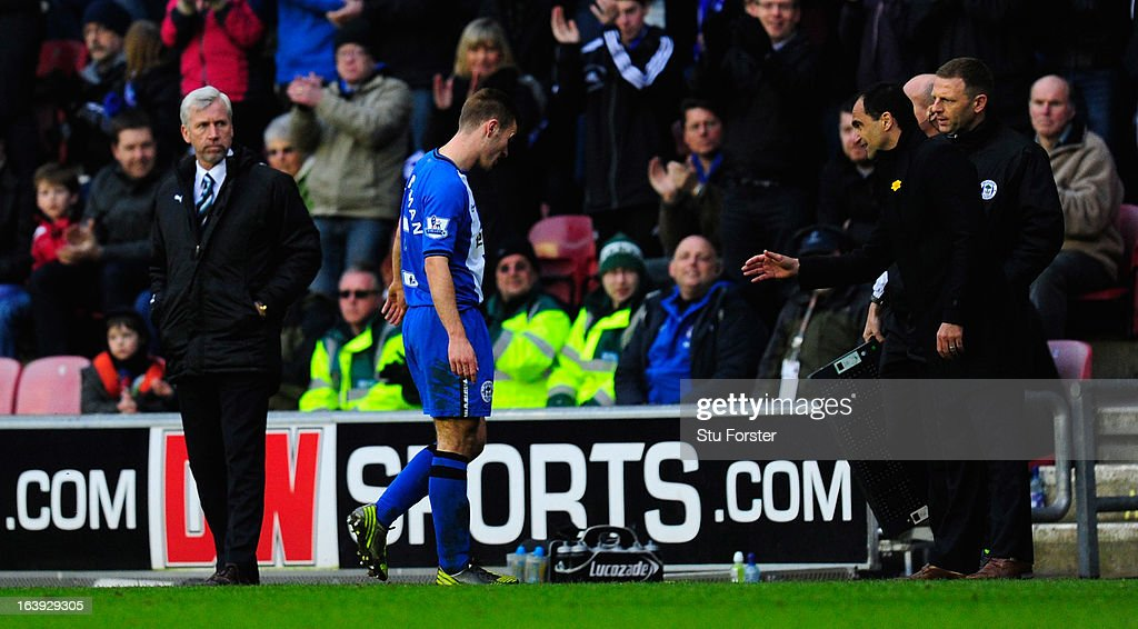 Newcastle manager Alan Pardew (l) looks on as Callum McManaman (c) is substituted as Wigan manager Roberto Martinez (r) reacts during the Barclays Premier League match between Wigan Athletic and Newcastle United at DW Stadium on March 17, 2013 in Wigan, England.