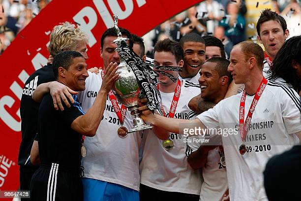 Newcastle manager Chris Hughton recieves the trophy from Nicky Butt as Newcastle are crowned champions of the Championship after the Coca Cola...
