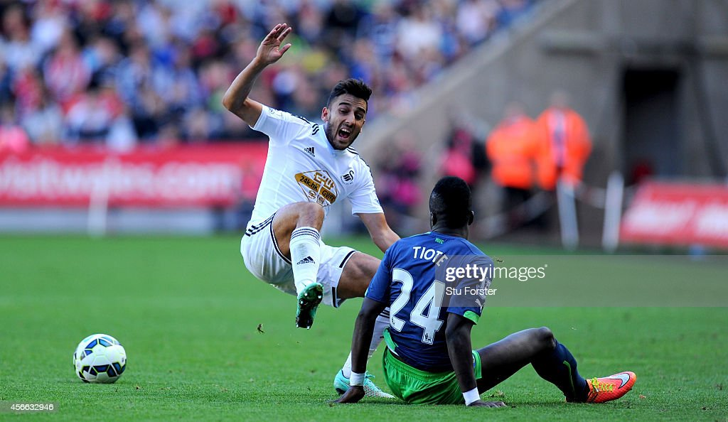 Newcastle player Chieck Tiote (r) beats Neil Taylor to the ball during the Barclays Premier League match between Swansea City and Newcastle United at Liberty Stadium on October 4, 2014 in Swansea, Wales.