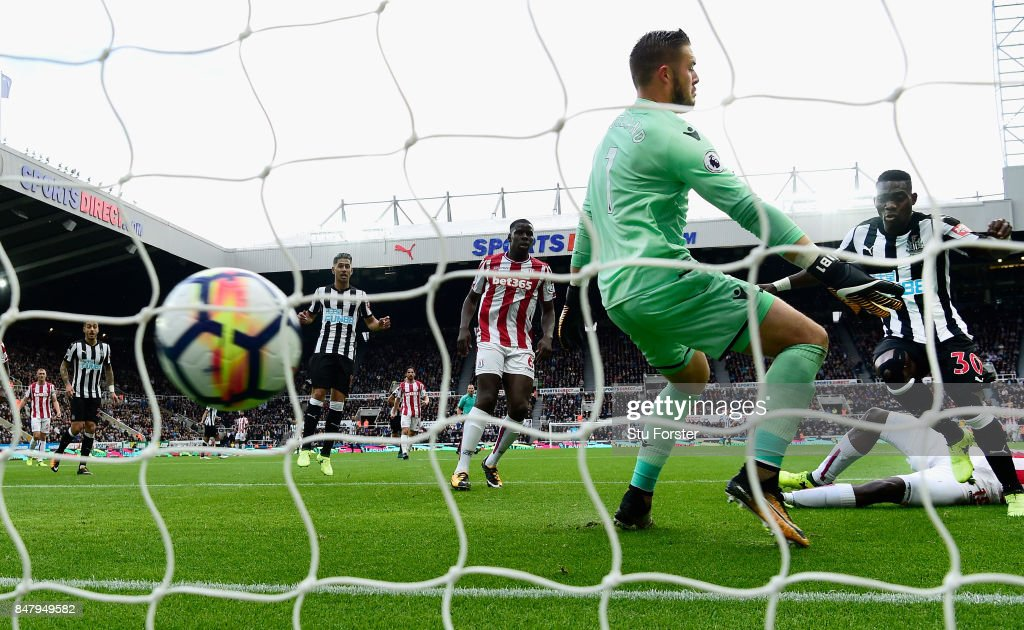 Newcastle player Christian Atsu (r) scores the opening goal past Jack Butland during the Premier League match between Newcastle United and Stoke City at St. James Park on September 16, 2017 in Newcastle upon Tyne, England.