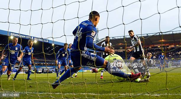 Newcastle player Daryl Murphy scores the opening goal past Birmingham defender Che Adams on the goalline as striker Aleksandar Mitrovic is injured...