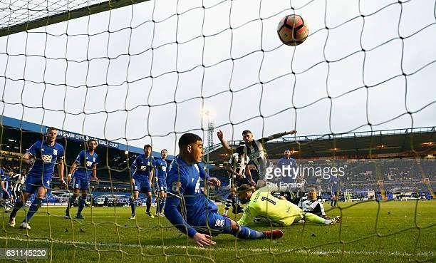 Newcastle player Daryl Murphy scores the opening goal past Birmingham defender Che Adams on the goalline as striker Aleksandar Mitrovic is injured...