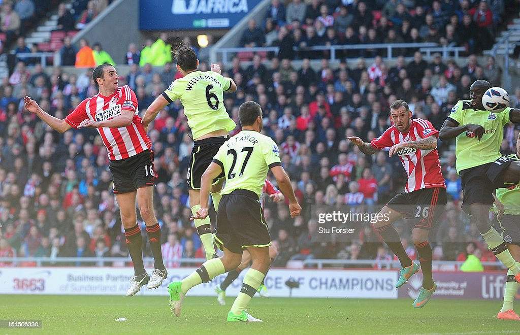 Newcastle player Demba Ba (r) deflects the ball for Sunderlands equaliser from a John O' Shea header during the Barclays Premier league match between Sunderland and Newcastle United at Stadium of Light on October 21, 2012 in Sunderland, England.