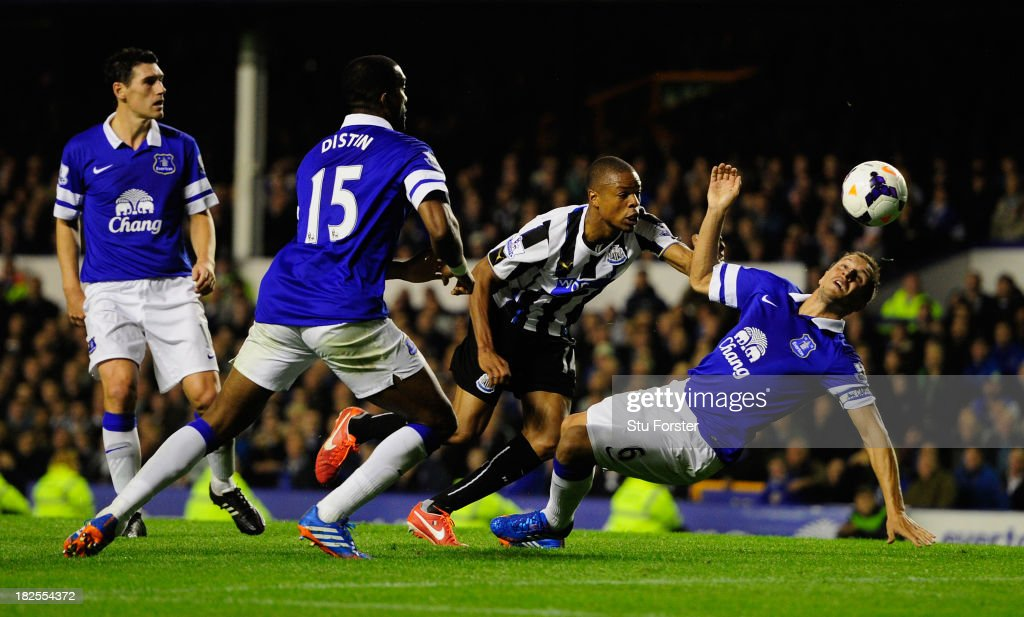 Newcastle player Loic Remy beats Phil Jagielka to score the second newcastle goal during the Barclays Premier League match between Everton and Newcastle United at Goodison Park on September 30, 2013 in Liverpool, England.