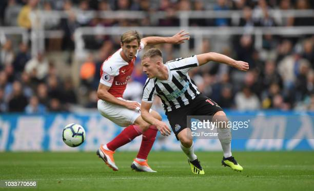 Newcastle player Matt Ritchie is challenged by Nacho Monreal of Arsenal during the Premier League match between Newcastle United and Arsenal FC at St...