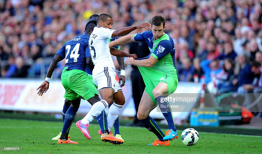 Newcastle player Mike Williamson (r) is tugged by Swansea player Wayne Routledge (c) during the Barclays Premier League match between Swansea City and Newcastle United at Liberty Stadium on October 4, 2014 in Swansea, Wales.