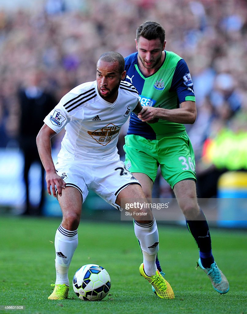 Newcastle player Paul Dummett (r) is held off by Jazz Richards during the Barclays Premier League match between Swansea City and Newcastle United at Liberty Stadium on October 4, 2014 in Swansea, Wales.