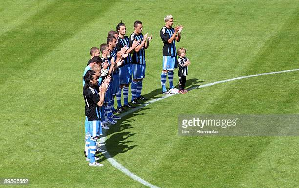 Newcastle players observe a minute's applause in memory of Sir Bobby Robson prior to the preseason friendly match between Dundee United and Newcastle...