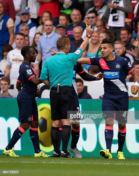 Newcastle striker Aleksandar Mitrovic is booked by referee Michael Jones during the Barclays Premier League match between Swansea City and Newcastle...