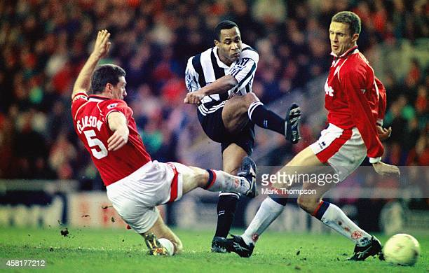 Newcastle striker Les Ferdinand shoots to score the winning goal despite the attempts of the Middlesbrough defenders Nigel Pearson and Steve Vickers...