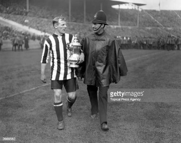 Newcastle United captain Frank Hudspeth is escorted from the pitch with the FA Cup trophy after Newcastle United's 20 victory over Aston Villa in the...