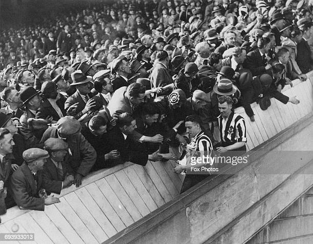 Newcastle United captain Jimmy Nelson carrying the trophy and followed by two goal scoring forward Jack Allen are congratulated by fans after the...