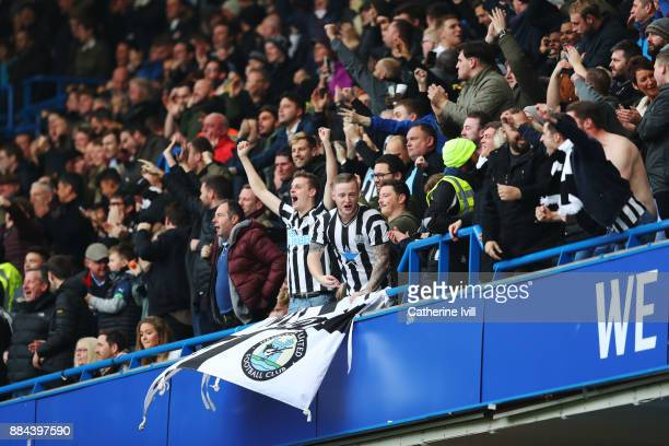 Newcastle United fans celebrate their sides first goal during the Premier League match between Chelsea and Newcastle United at Stamford Bridge on...
