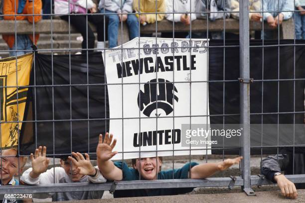 Newcastle United fans hang their flags to the safety fence surrounding the pitch before a First Division match against Liverpool at St James' Park on...