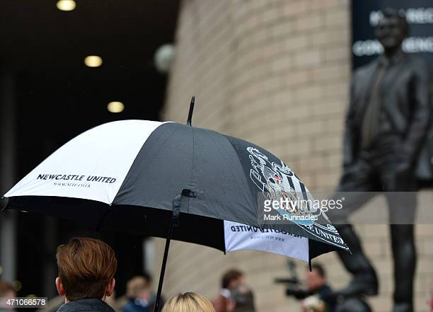 Newcastle united fans hide from the driving rain under umbrellas before the start of the Barclays Premier League match between Newcastle United and...