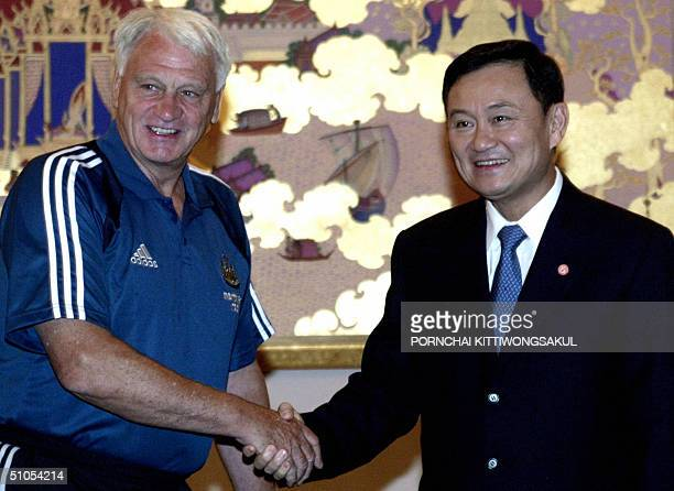 Newcastle United football team manager Sir Bobby Robson shakes hands with Thai Prime Minister Thaksin Shinawatra at the Government House in Bangkok...