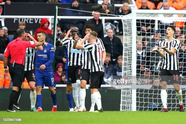 Newcastle United players confront referee Paul Tierney after he awards Chelsea a penalty during the Premier League match between Newcastle United and...